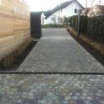 Aménagement d'une entrée: nouveau pavage, clôtures recouvertes de lierre et  jeunes graminées
